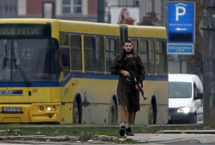 A gunman with an automatic weapon walks in Sarajevo, after he fired shots at the U.S. embassy