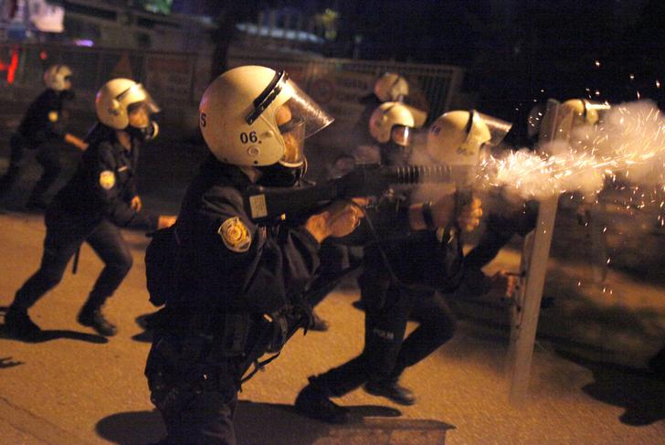A riot police officer fires tear gas at anti-government protesters during a protest in Kennedy street in central Ankara
