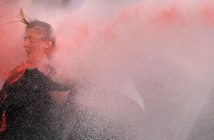 A woman is attacked by water cannon during protests in Kizilay square in central Ankara