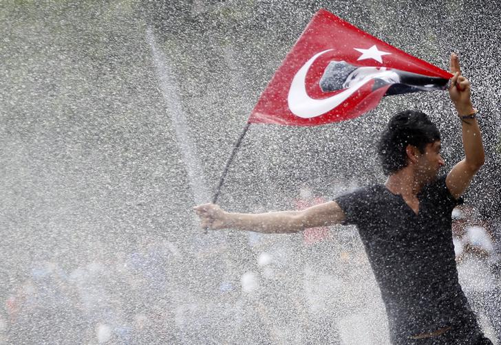 A protester is attacked by water cannon during crowds in Kizilay square in central Ankara