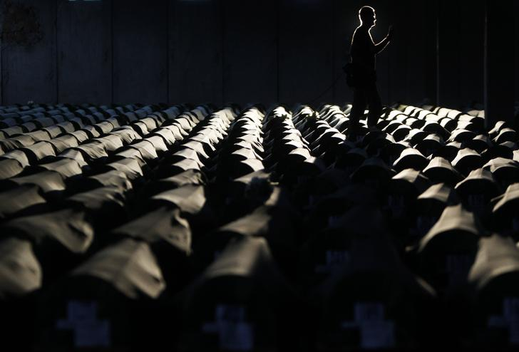 A Bosnian man walks near the 409 coffins of newly identified victims of the 1995 Srebrenica massacre in Potocari
