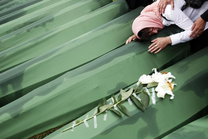 A Bosnian woman cries on the coffin of a relative, which is one of the 409 coffins of newly identified victims from the 1995 Srebrenica massacre